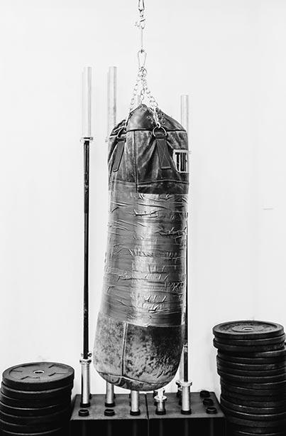 Boxing bag, barbells, weight-lifting plates at tribestrength.
